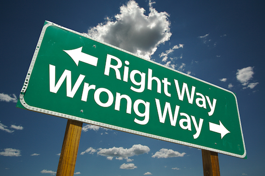 """Right Way, Wrong Way"" Road Sign with dramatic blue sky and clouds."